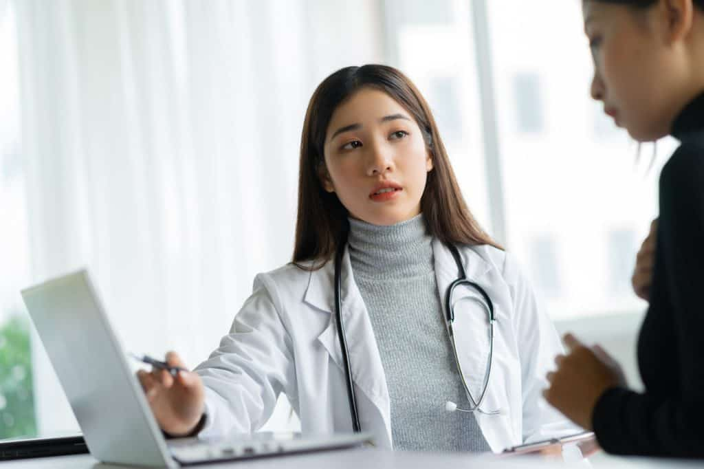 Asian Femal Gynocologist Talking to Patient